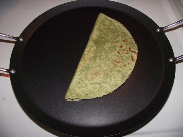 Quesadilla after the first turn, nicely browned with melted cheese.